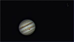 Une autre image de Jupiter. On y distingue la grande tâche rouge, un cyclone géant plus grand que la terre ainsi que les satellites Io et Europe (en haut à droite)